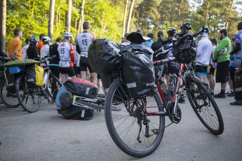 Rower z sakwami na tle grupy ludzi