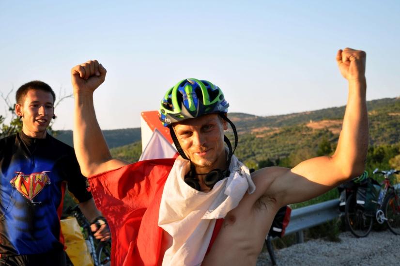 Mężczyzna z flagą w geście pokazującym siłę